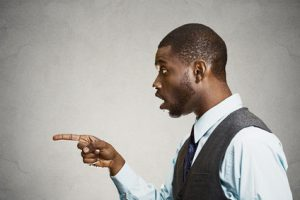 Surprised man pointing with finger at someone, something